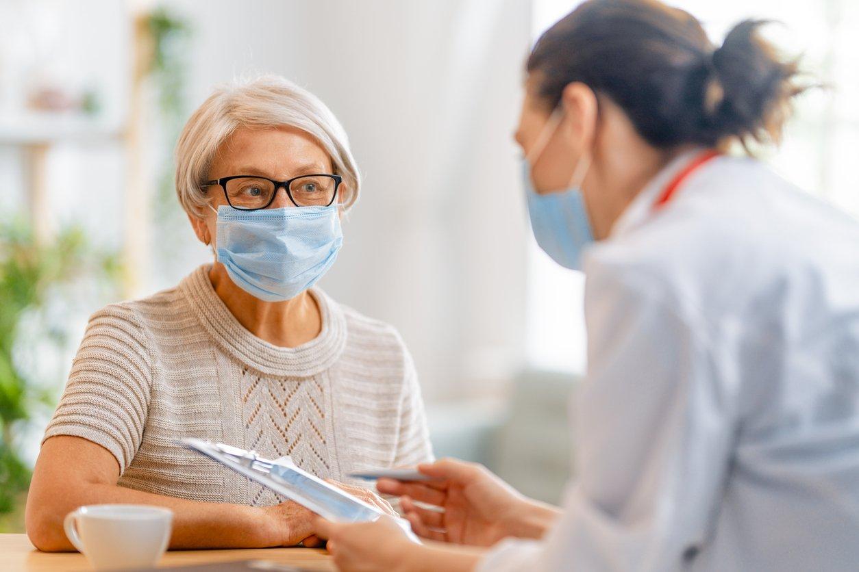 Médica-e-senhora-usando-mascaras-em-consulta-medica