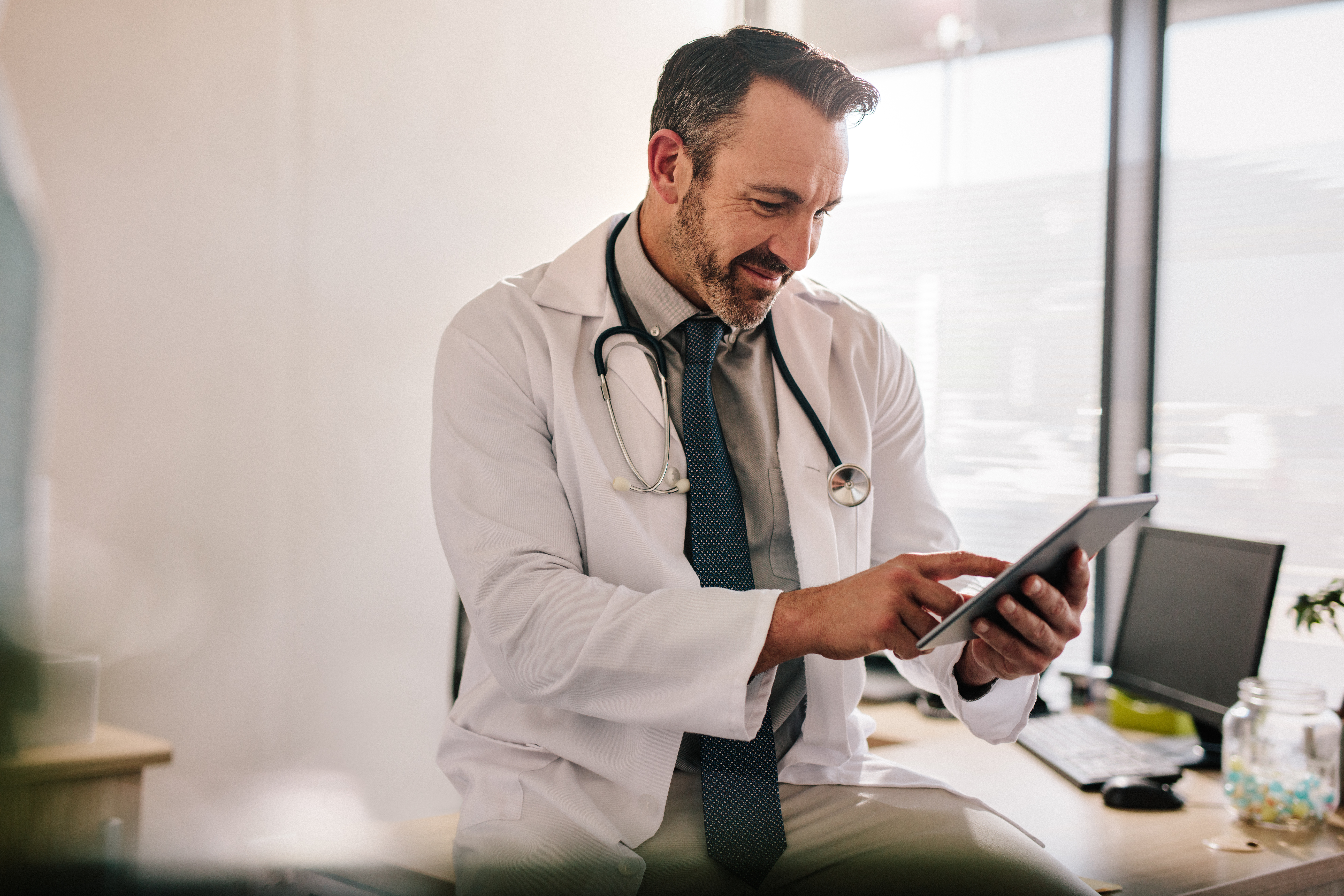 Doctor-using-digital-tablet-at-his-clinic-1132442656_7888x5259