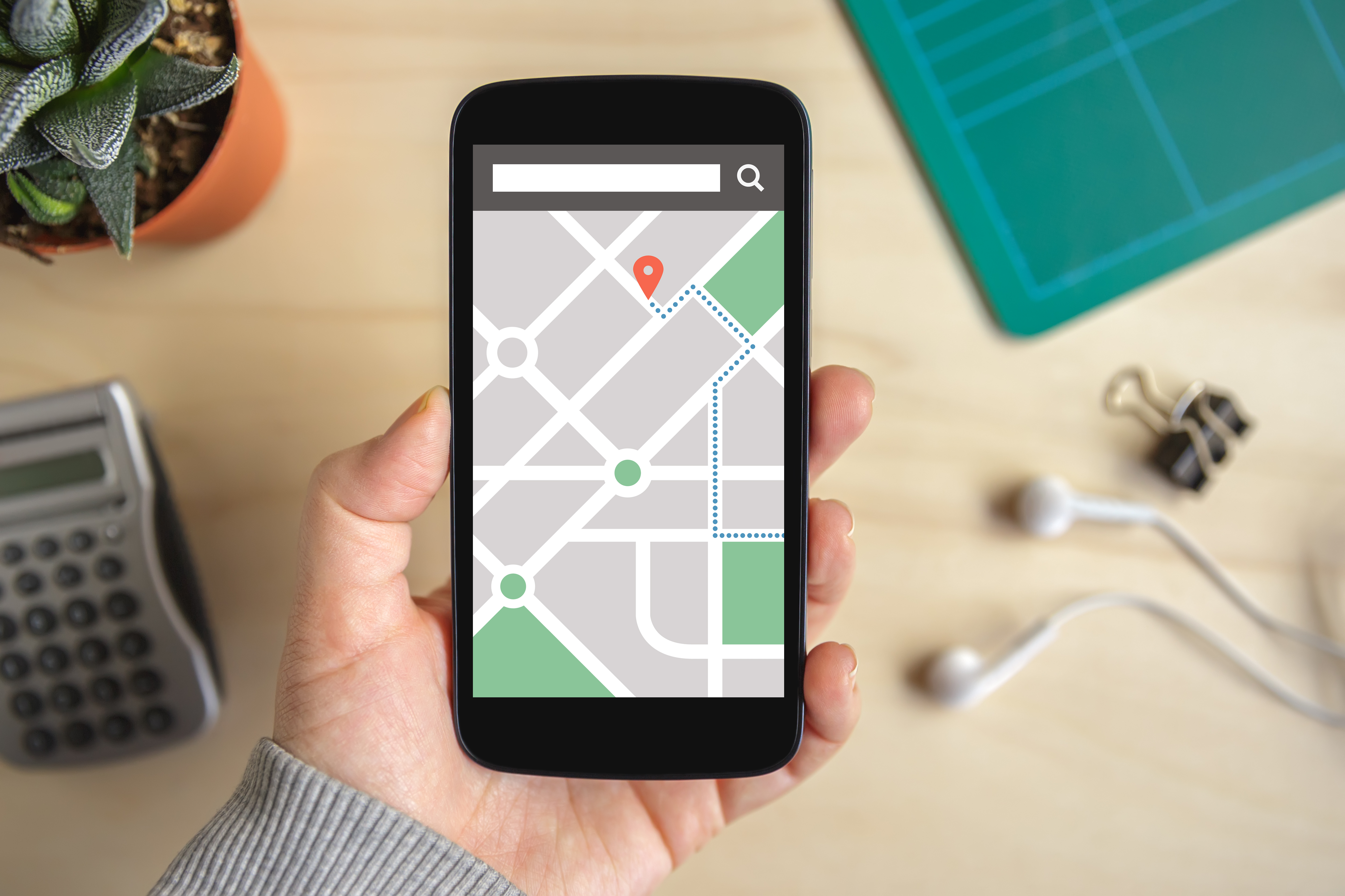 Hand-holding-phone-with-map-gps-navigation-application-on-screen-527522894_5000x3333